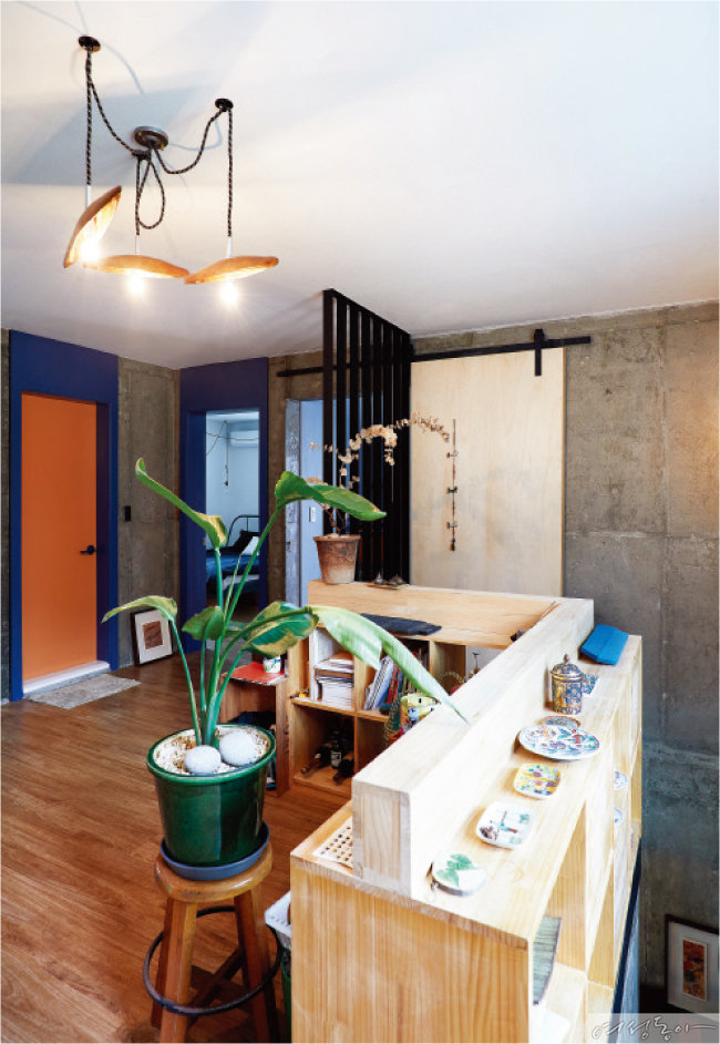 2층 계단 난간에는 나무로 수납장을 만들고 여행지에서 모은 도자기를 전시해두었다. 나무를 깎아 만든 조명도 눈여겨볼 것.