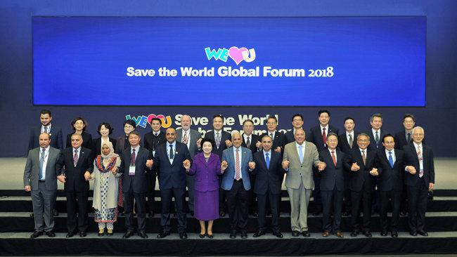 '2018 세이브더월드 국제포럼'을 통해 긴급구호와 글로벌 파트너십을 주제로 한자리에 모인 장길자 위러브유 회장과 아델 모하마드 아다일레 주한 요르단 대사, 주한 외교관 및 각계 인사들이 글로벌 협력의 의미로 손을 맞잡고 있다.