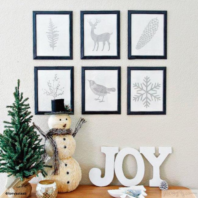 겨울을 상징하는 사슴, 솔방울, 눈 결정 등의 일러스트 액자로 꾸민 벽 데코. 탁자에는 눈사람, 트리, 'JOY' 장식으로 아기자기한 느낌을 더했다.