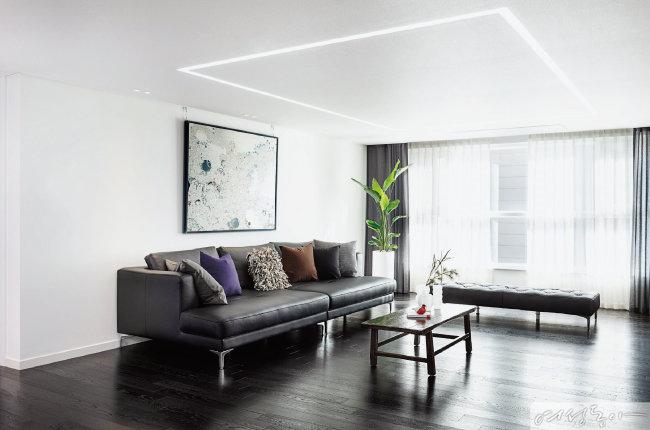 바닥과 소파는 블랙, 벽과 천장은 화이트로 꾸며 블랙 & 화이트 인테리어의 매력을 보여주는 거실. 액자는 오픈갤러리, 테이블 위 새 오브제는 이딸라, 화병은 류종대 & 유남권 작가 작품, 소파는 자코모by조희선뮬