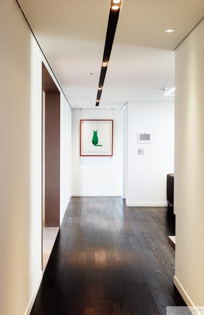 현관에서 거실로 이어지는 복도. 오픈갤러리의 박경묵 작가 그림을 달아 감각적인 공간을 완성했다. 복도를 따라 길게 매입등을 설치해 갤러리처럼 연출한 것도 눈여겨볼 것.