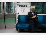 한 노인이 지하철 노약자석에서 휴대전화를 들여다보고 있다. [뉴스1]