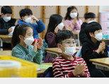 지난 2월 초 서울 시내 한 초등학교에서 학생들이 마스크를 쓴 채 교실에 앉아 있다. [뉴스1]