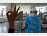 오늘도 웃으면서!경북대병원 집중치료실에서 간호사들이 환자를 돌보다가 밖에 있는 동료와 사인을 주고 받으며 웃고 있다. [뉴시스]