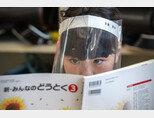 일본 닛코 - 6월 03일 : 플라스틱 페이스 바이저를 착용한 학생이 2020년 6월 3일 일본 닛코에 있는 기누가와 초등학교에서 수업을 듣고 있다. 교실에서의 사회적 거리 두기, 손 세정제 사용, 안면 마스크 사용, 플라스틱 페이스 바이저 사용 등 안전 대책이 시행되고 있다.