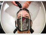 마스크와 투명 얼굴 보호막으로 중무장한 채 머리를 감고 있는 모습.