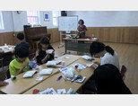 서울 용산구에 있는 H아동복지시설 봉사자가 아이들과 함께 인형 만들기를 하고 있다.  [H아동복지시설 제공]