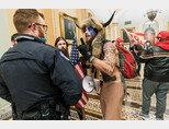 1월 6일(현지시각) 미국 워싱턴 연방의회 의사당에 난입한 '큐어넌' 회원 제이크 앤절리(뿔 달린 모자를 쓴 이)가 경찰관과 대치하고 있다. [AP=뉴시스]