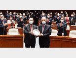 국민의힘 김종인 전 비상대책위원장(오른쪽)이 4월 8일 서울 여의도 국회에서 열린 의원총회에 참석해 기념패를 들고 사진 촬영을 하고 있다. [뉴시스]