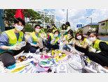 ASEZ WAO 회원들이 판교 백현동카페문화거리 일대를 정화한 후, 폐현수막을 활용해 수거한 쓰레기 중 플라스틱과 아닌 것을 나누고 있다. 이날 행사에는 한선미 성남시의원(앞줄 왼쪽 세 번째)도 함께했다.