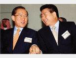 2002년 9월 29일 부산아시아드주경기장에서 열린 아시안게임 개막식에 참석한 당시 한나라당 이회창 대선후보(왼쪽)와 새천년민주당 노무현 대선후보가 손을 잡은 채 이야기를 나누고 있다. [동아DB]