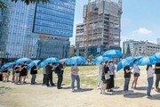 폭염 뚫고… 검사소 앞 '우산 행렬'