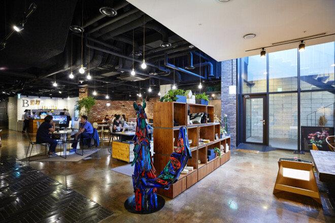 계단을 내려와 만나게 되는 기념품 가게와 꽃집, 카페와 레스토랑이 어우러진 개방형 공간. 천장의 파이프라인 구조를 그대로 노출해 공간감을 확장했다.