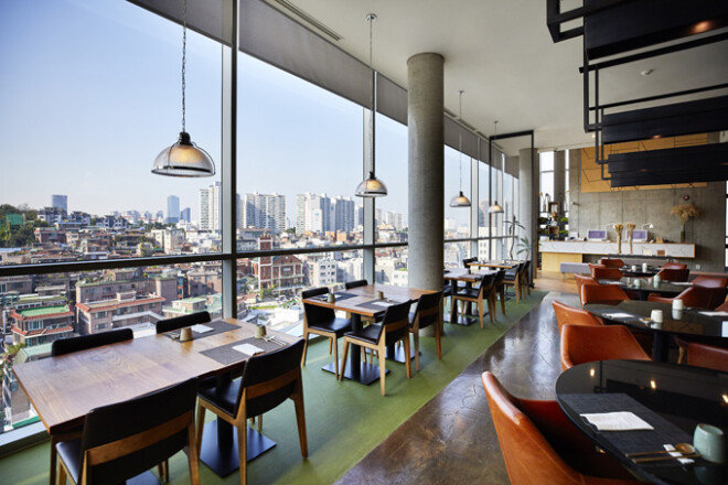 9층 로비에 위치한 한식 레스토랑 '나루'의 통유리로 내려다보이는 상도동 주택가 풍경. 1950~2000년대까지 한국 주택 건축양식이 파노라마처렴 펼쳐진다.