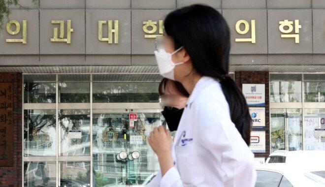 정부의 공공의대 신설 정책 등에 반발해 전국의사 총파업이 진행된 가운데, 8월 28일 오후 대전에 위치한 의과대학 앞으로 의료진이 마스크를 쓰고 지나고 있다.  [뉴스1]