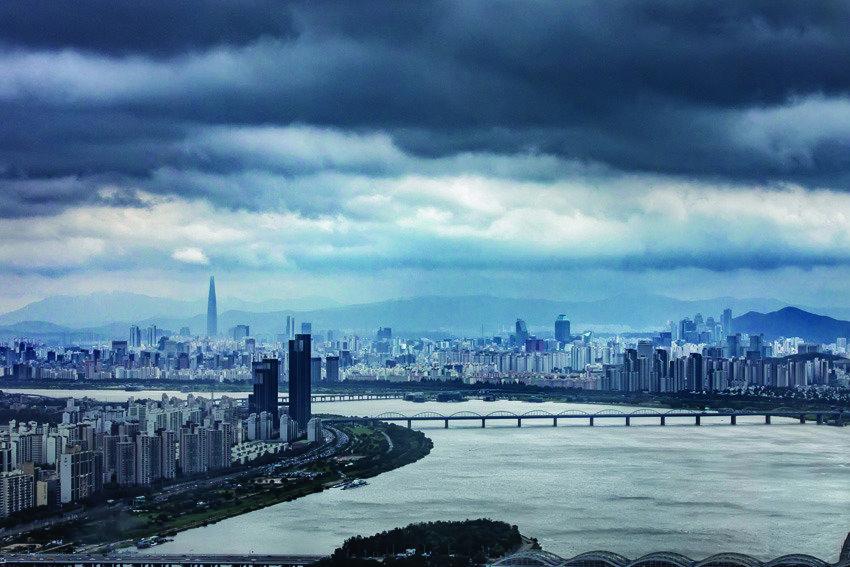 먹구름 아래 숨죽인 무채색 도시