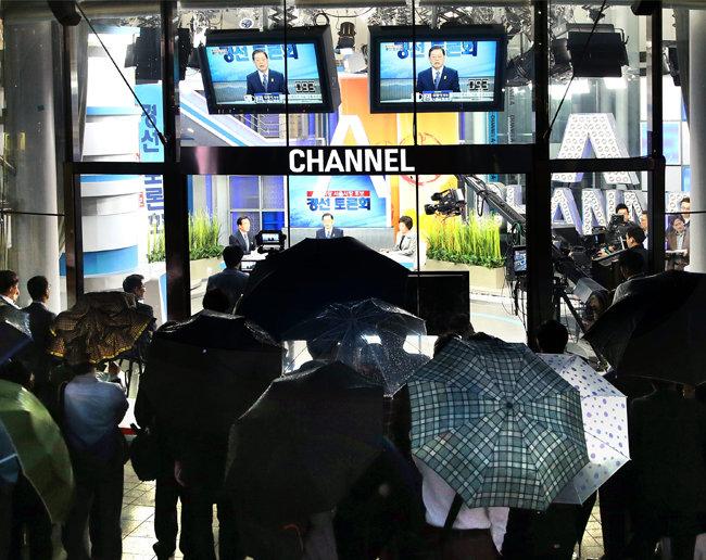 2014년 5월 11일 서울 청계천로 동아미디어센터 오픈스튜디오에서 진행된 모정당 서울시장 경선 후보 TV토론회를 시민들이 우산을 받쳐든 채 지켜보고 있다,[양회성 동아일보 기자]
