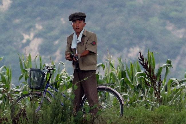 지난해 7월 26일 중국 랴오닝성 단둥시 압록강 너머 신의주 외곽에서 한 북한 국경경비대원이 중국인 관광객과 취재기자를 향해 총을 겨누고 있다. [변영욱 동아일보 기자]