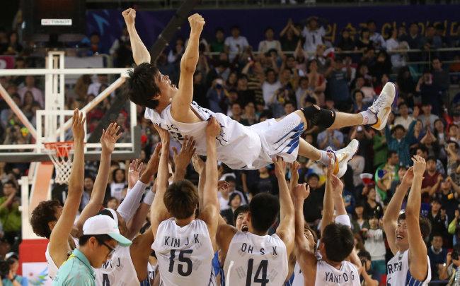 2014년 10월 3일 열린 인천아시아경기대회 남자농구 결승에서 한국이 이란을 꺾고 우승을 확정 지은 후 선수들이 김주성 선수를 헹가래 치고 있다. [동아DB]
