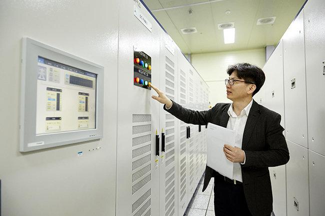 효성의 한 직원이 평창풍력단지에 설치된 ESS(에너지저장장치)의 일부인 PCS(전력변환장치)를 살펴보고 있다. [사진제공·효성]