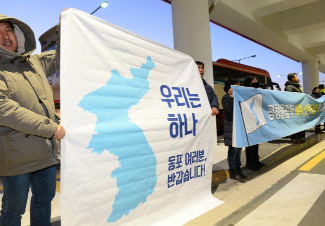 북한 선수단 본진 32명이 2월 1일 양양공항에 도착한 가운데 환영 나온 6·15 남측위원회 회원들이 플래카드를 들어 보이고 있다.