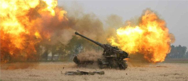북한군 장거리 포병부대의 포 발사 장면. [노동신문, 동아DB]
