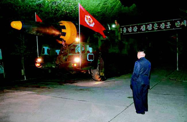 북한은 2017년 5월 15일 지대지 중장거리 전략탄도로켓(IRBM)인 '화성-12형'의 시험발사에 성공했다. 김정은 국무위원장이 '화성-12형'을 지켜보고 있다.(사진촬영 일시 미상) [노동신문]