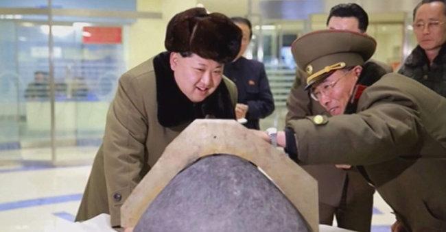 대륙간탄도미사일 탄두를 보며 웃고 있는 김정은의 모습을 전한 북한 노동신문 2016년 3월 15일자 사진. [동아DB]