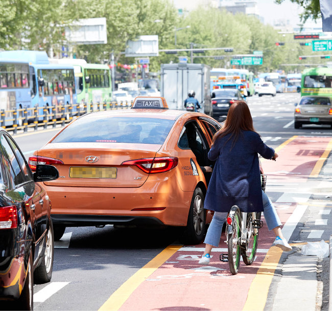 종각역 부근 자전거전용차로를 침범해 승객을 하차시키는 택시. 택시는 종로 자전거 전용차로를 침범해선 안 되고, 택시 승강장에서만 승객을 태우거나 내려줘야 한다. [홍중식 기자]