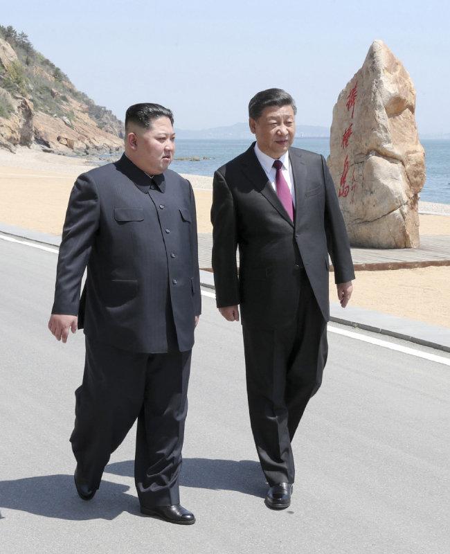 김정은 북한 국무위원장과 시진핑 중국 국가주석이 5월 8일 중국 랴오닝성 다롄시 방추이섬 해변을 함께 걸으며 대화하고 있다. [다롄=신화 뉴시스]