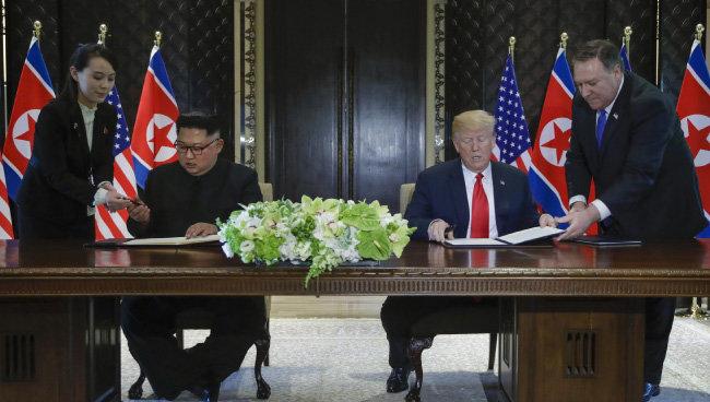 6월 12일 김정은 북한 국무위원장과 트럼프 미 대통령이 공동성명에 서명하고 있다. 이에 보수정당인 자유한국당은 트럼프를 비난했다. [AP 뉴시스]