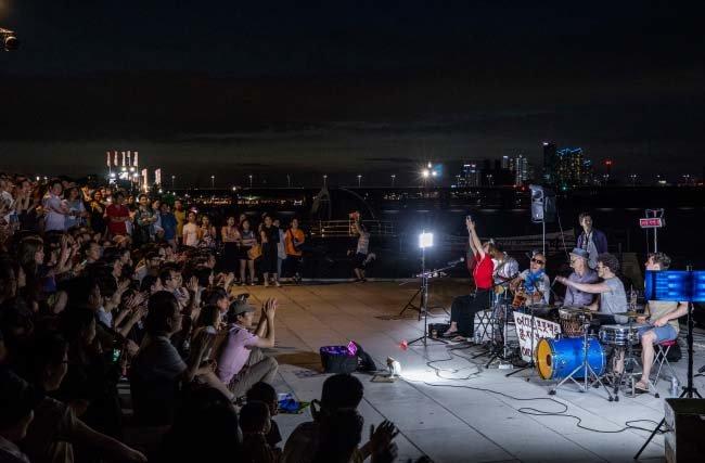 한밤의 열기를 북돋우는 버스킹 '어디든 프로젝트'의 공연을 즐기는 시민들.