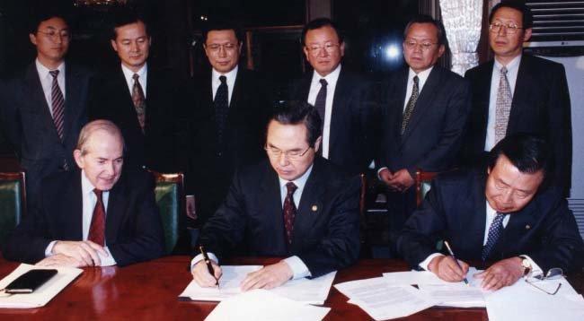 1997년 12월 3일 임창렬 경제부총리(가운데)와 이경식 한국은행 총재(오른쪽)가 국제통화기금(IMF) 미셸 캉드시 총재가 지켜보는 가운데 IMF국제금융 합의문서에 서명하고 있다.