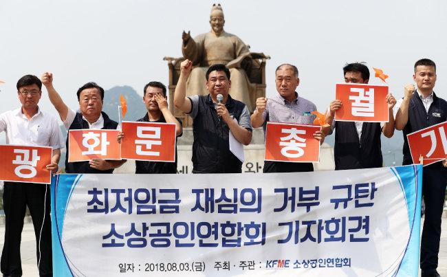 """최승재 소상공인연합회 회장(왼쪽 네 번째)과 회원들이 8월 3일 서울 종로구 광화문광장에서 열린 최저임금 재심의 거부 규탄 기자회견에서 구호를 외치고 있다. 소상공인연합회는 이 자리에서 """"소상공인들의 분노를 모아 오는 8월 29일 '전국 소상공인 총궐기'에 나서는 등 직접 행동에 돌입하겠다""""고 밝혔다. [뉴스1]"""