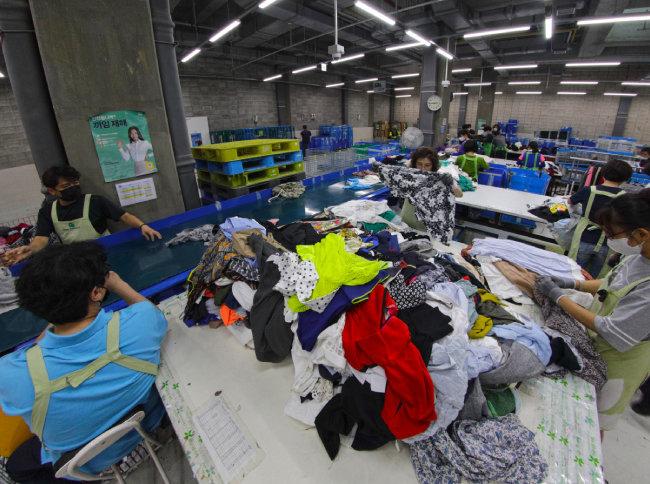 의류 재활용을 위해 수거된 옷가지를 분류하는 모습.