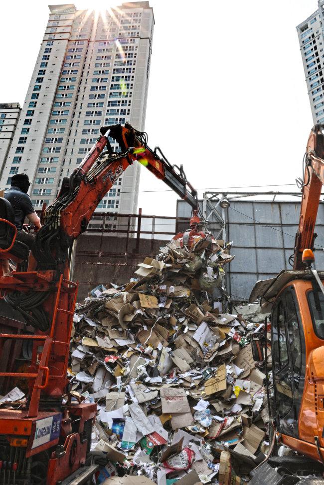 폐지를 수거하는 작업 뒤로 우뚝 솟은 고층건물. 물질문명의 묘한 대비 같다.