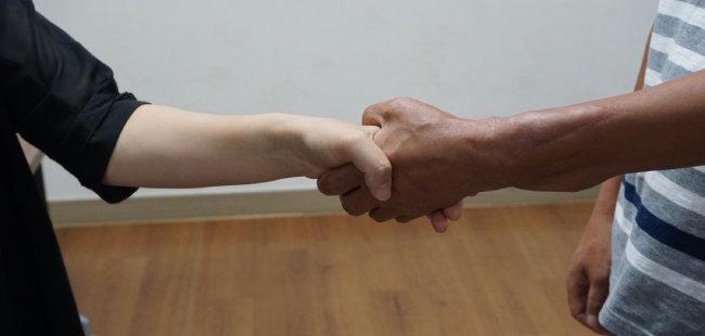 팔이식 수술을 받은 왼손으로 기자의 손을 단단하게 마주 잡은 손진욱 씨(오른쪽). 그의 왼팔은 지금 과거의 힘을 70% 정도 회복했다. [사진제공·W병원]