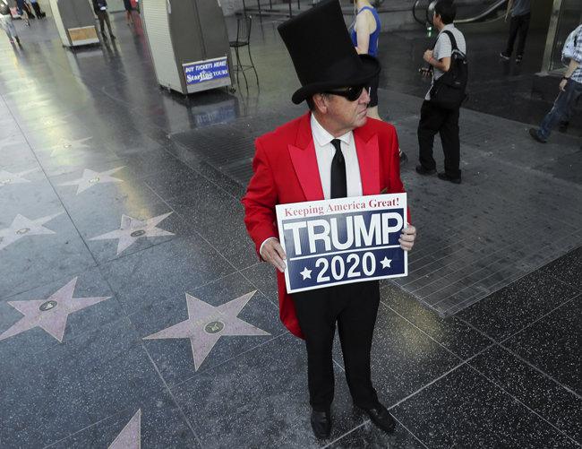 7월 25일(현지 시간) 미국 로스앤젤레스 '할리우드 명예의 거리' 바닥에 설치된 도널드 트럼프 대통령의 별 모양 기념판이 완전히 파손된 가운데, 그 현장에 한 트럼프 대통령 지지자가 '미국을 계속 위대하게—트럼프 2020'이라는 글귀가 적힌 피켓을 들고 서 있다. [AP=뉴시스]