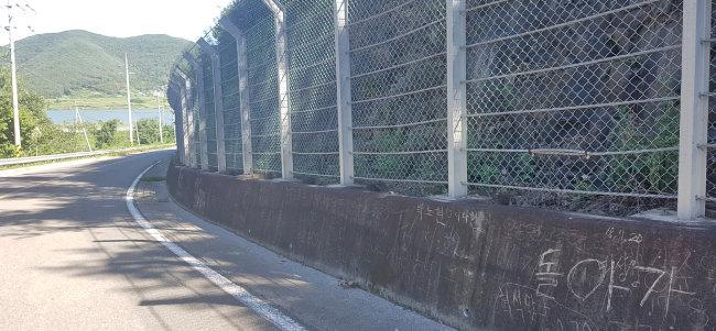 오르막길인 박진고개 벽의 긁힌 자국들과 자전거 동호인들이 쓴 낙서.
