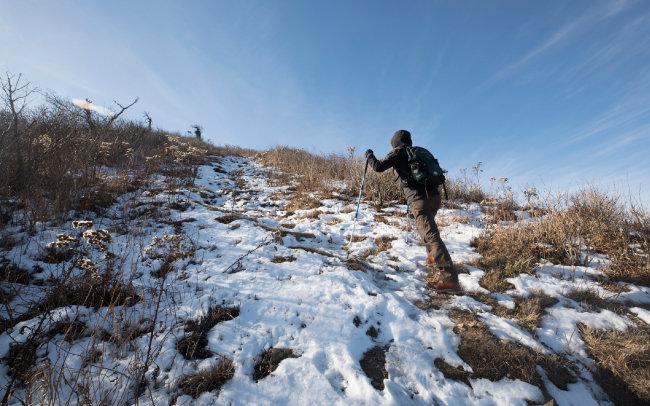 눈이 소복이 쌓인 길을 걷는 등산객.