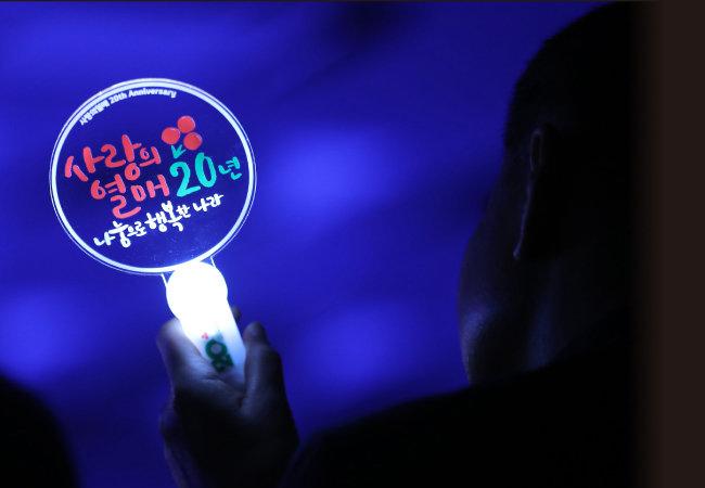 1998년 국내 최초 법정모금기관으로 설립된 사랑의열매 사회복지공동모금회 창립 20주년을 맞아 11월 12일 열린 기념식에서 한 참석자가 기념 야광봉을 흔들고 있다. [뉴스1]