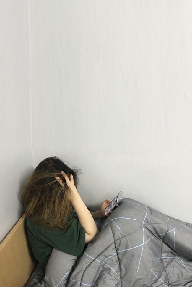한 여자 대학생이 잠자리에 들기 전 인스타그램을 보면서 우울감을 느끼는 모습.