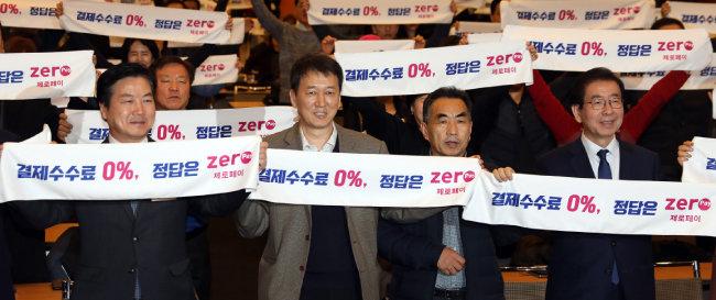 박원순(오른쪽) 서울시장과 소상공인들이 지난해 12월 20일 서울 중구 대한상공회의소 국제회의장에서 열린 제로페이 이용 확산 결의대회에서 '결제 수수료 0%, 정답은 제로페이' 펼침막을 들고 있다. [뉴시스]