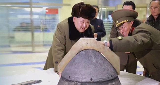김정은 북한 국무위원장이 2016년 3월 15일 대기권 재진입 고열 실험을 견뎌낸 미사일 탄두 부분을 살펴보며 웃고 있다. [동아DB]