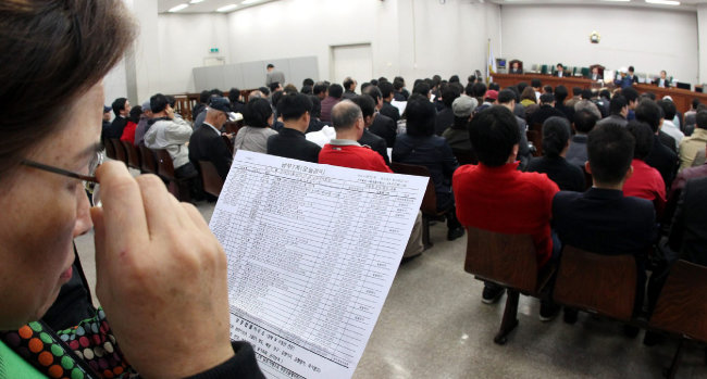 서울남부지법의 부동산 경매법정에서 좌석이 부족해 뒤편에 선 사람들이 경매 진행 상황을 지켜보고 있다. [장승윤 동아일보 기자]