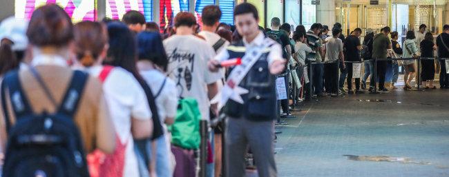 2018년 6월 6일 오전 서울 중구 롯데면세점 본점 입구에서 중국인 관광객들이 면세점 개점을 기다리며 줄을 서 있다. [뉴스1]