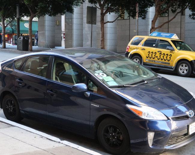 샌프란시스코 시내 한 일방통행 도로 양쪽에 택시와 우버 차량이 각각 서 있다.