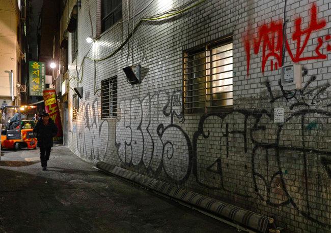 어둠이 내려앉은 을지로 골목에 청계천 재개발을 반대하는 벽보가 붙어 있다.
