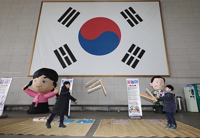 독립의 상징인 대형 태극기 앞에서 두 어린이가 윷놀이를 하고 있다.