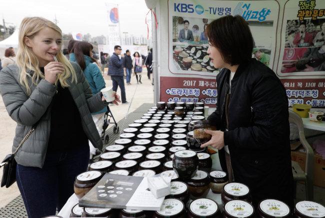 외국인 관람객이 한라산가마솥에서 만든 수제 조청을 맛보고 있다.